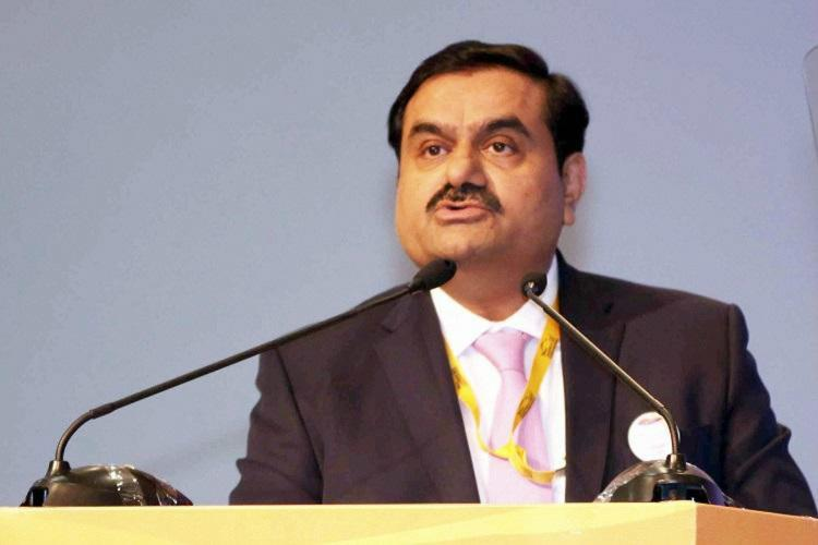 Gautam Adani standing at a podium and speaking He is wearing a black blazer with a white shirt and a baby pink tie
