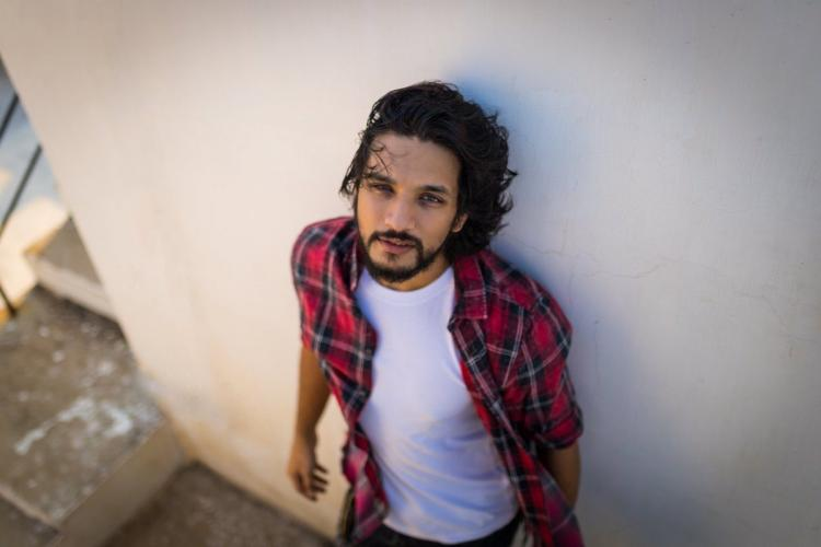 Shot from above actor Gautham Karthik is seen a red checked shirt worn over a plain white t-shirt