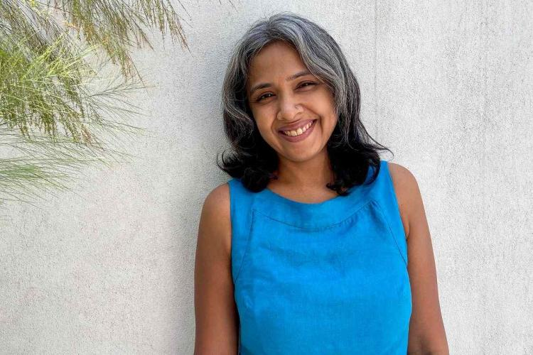 Gayathri in a sleeveless blue top with her grey-black short hair smiles standing against a white wall with one corner of it having a few stray leaves