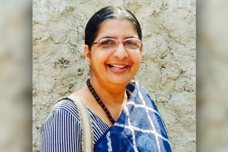 Geetha in a blue cotton sari and blouse a black beaded necklace and spectacles smiles directly at the camera