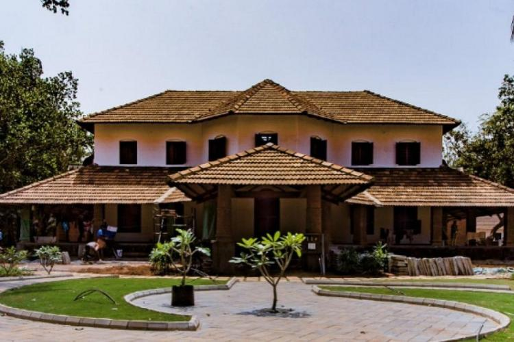 A traditional building of Kerala with roof tiles in two floors and the spacious front yard