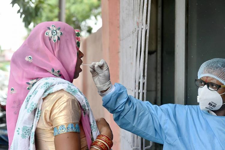A woman in Ghaziabad wearing a pink saree having her swab sample collected by a health worker