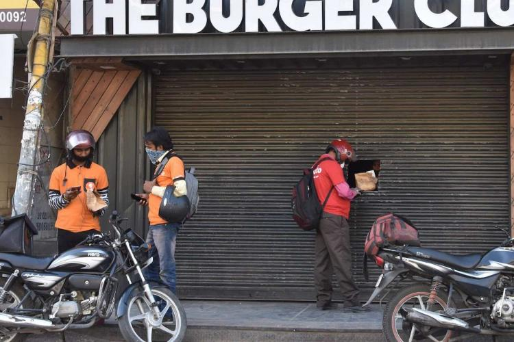 Gig workers from Swiggy and Zomato waiting for delivery in Burger shop