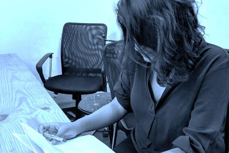 Representative image of a girl sitting at a table looking down at a piece of paper