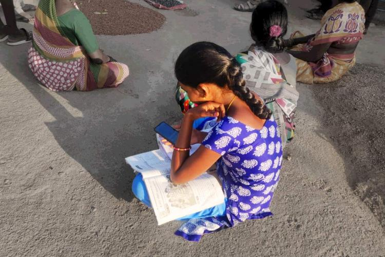 A young girl accessing online classes through smartphone
