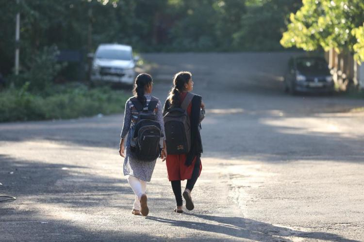 Two girls walking on the road with their school bags with their backs facing the camera
