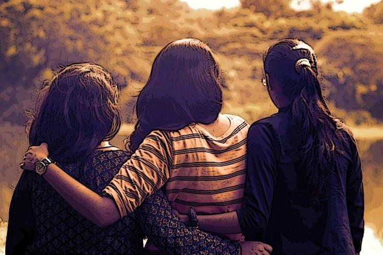 Image of three young women hugging each other and looking into the sun set