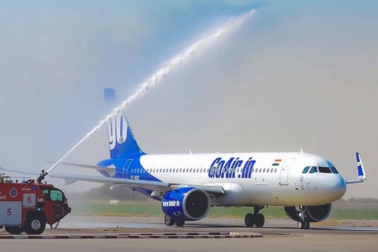 A GoAir plane being washed by a truck stream of water visible in the air from the truck