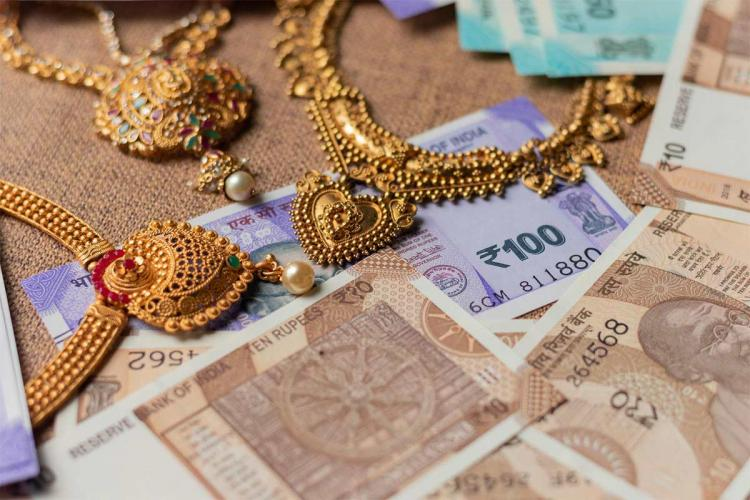 Gold jewellery and money kept on a surface