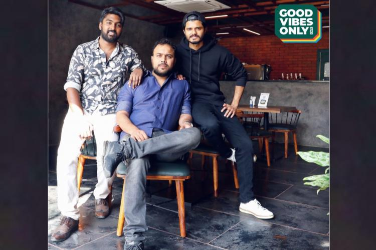 Good Vibes Only Cafe ambience in which Anand Devarakonda in a black shirt and a cap along with two other friends in casualas are seen