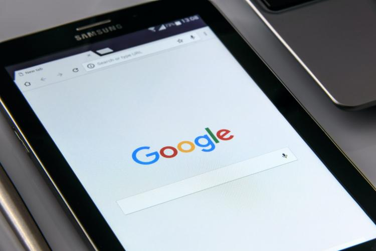 A mobile phone with the website opened to Google.com