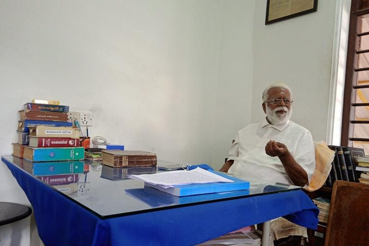 Gopalakrishnan an early man with white hair and beard and wearing a white shirt sits behind a desk thats covered with a blue sheet over which books are kept at one corner He gestures with his hand as he speaks