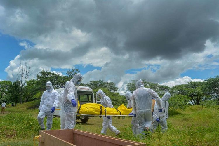 Civic workers, suited up in white hazmat suits, are carrying the dead body of a COVID-19 patient. The body is wrapped in a yellow plastic sheet and is being carried on a stretcher. A wooden coffin and an ambulance are seen in the image. The burial is happening in a vast field.