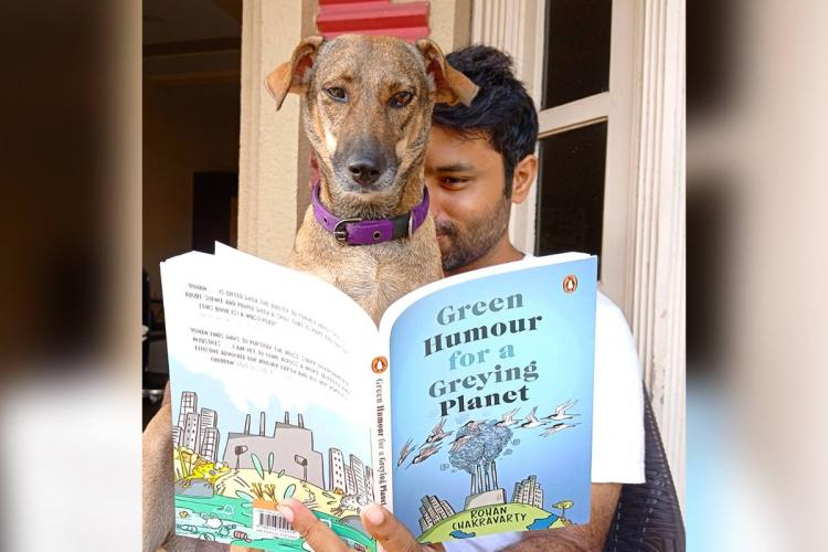 Rohan and his dog are sitting together he is holding his book Green Humour open and both are apparently reading it with the dog covering half of Rohans face