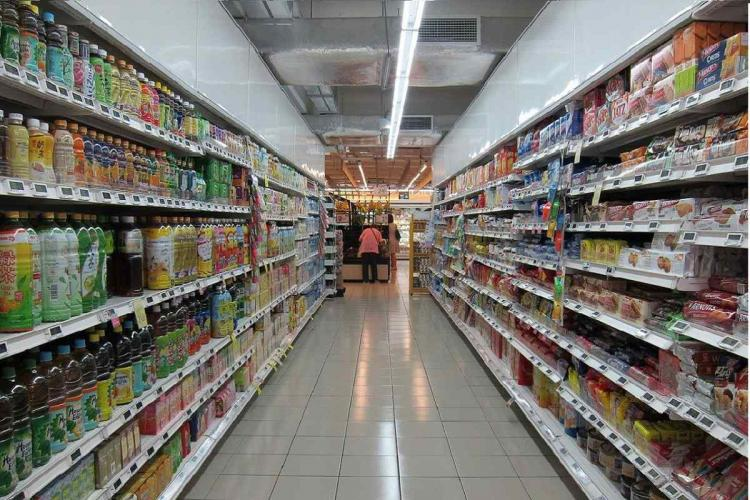 An empty grovery store aisle with foodstuffs on the shelves