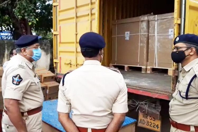 Cops in uniform checking the container from which the electronic goods were stolen