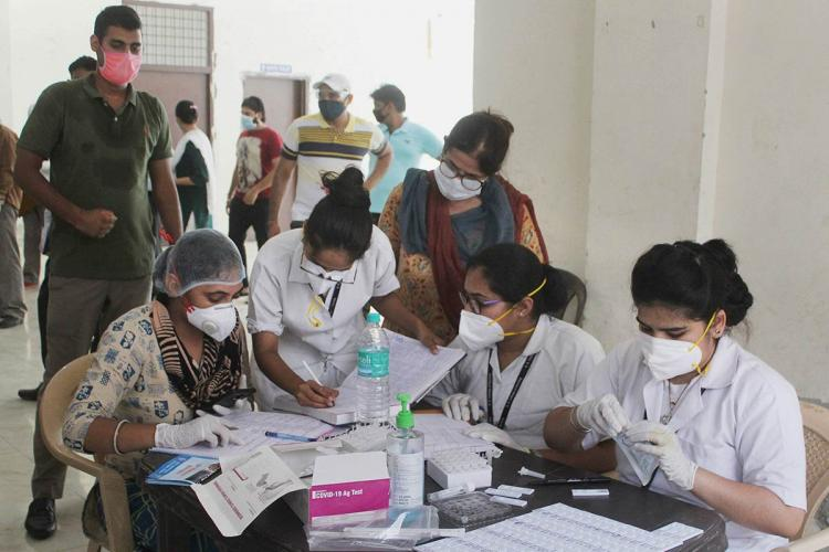 A group of healthworkers wearing masks sitting at a table working on covid tests