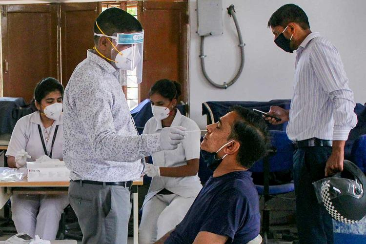 A man having his nasal swab collected by a health worker in a hospital