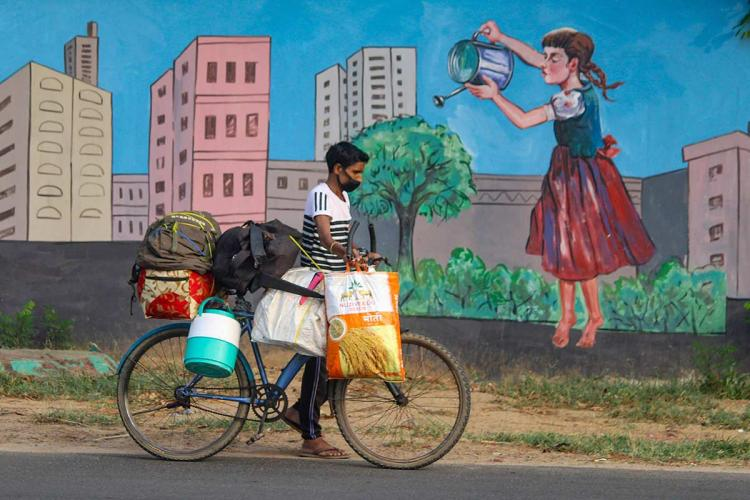A migrant worker in Gurugram with his belongings on a bicycle