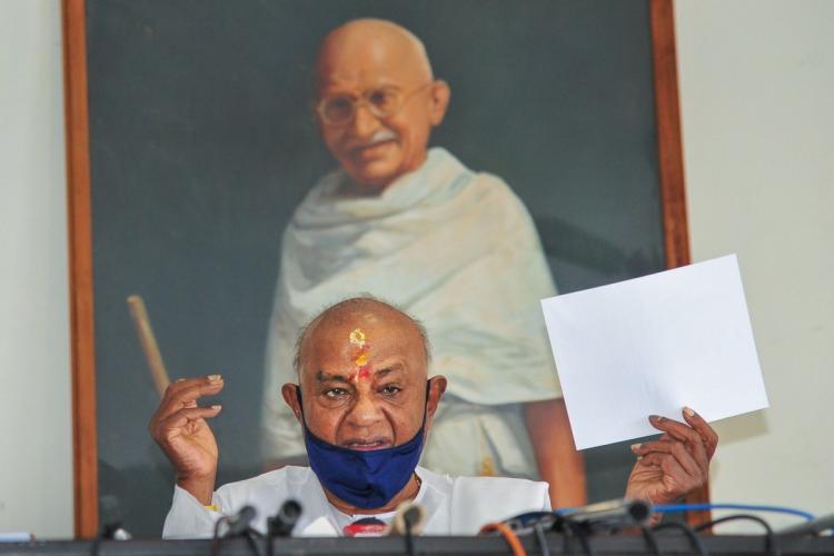 Former Prime Minister HD Devegowda sitting in front of Mahatma Gandhis portrait