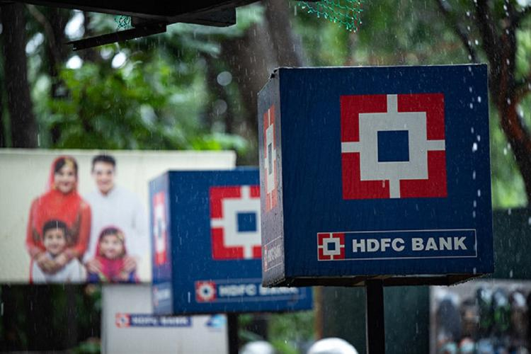 Signage of the HDFC Bank in blue and red placed on the road