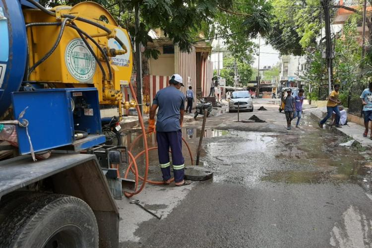 A worker clearing drains