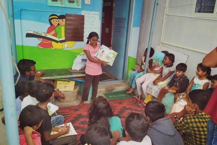 Child showing storybook to other children at Haadibadi community library