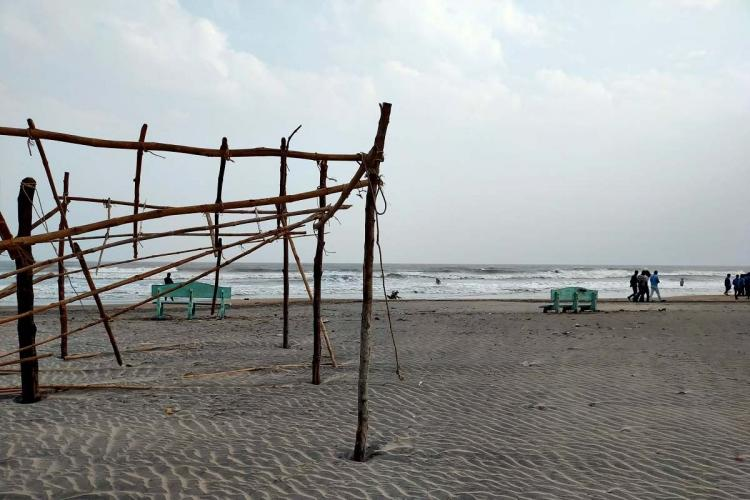 An erected wooden structure near Hamsaladeevi Beach with tourists walking on the shore