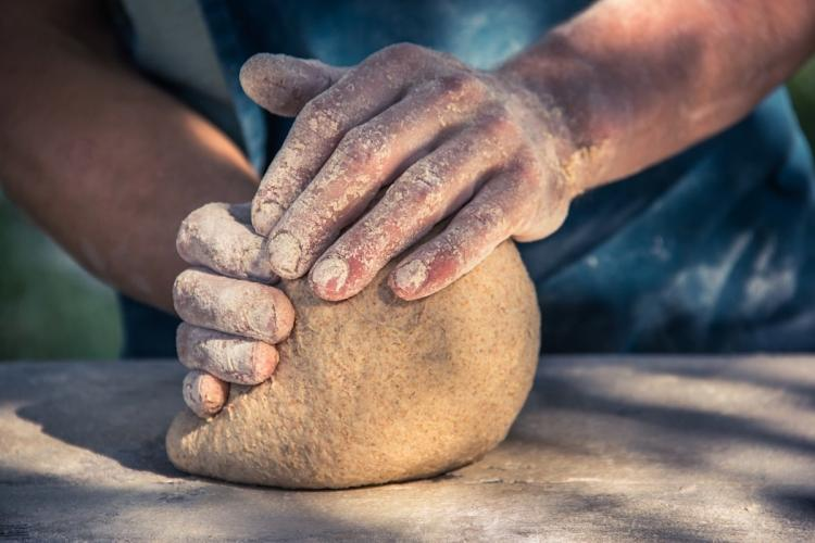 Mans hands rolling bread dough