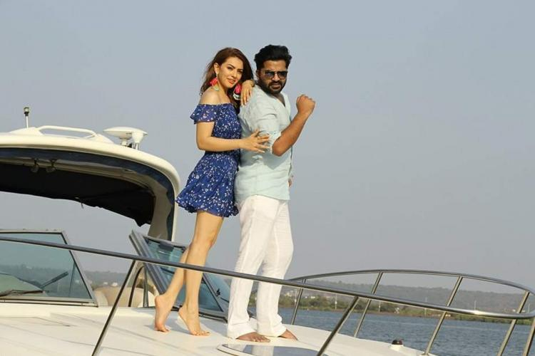 Hansika in a blue dress and STR in light colored T Shirt and pants on top of a boat