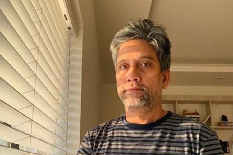 Professor Hany Babu standing next to a window