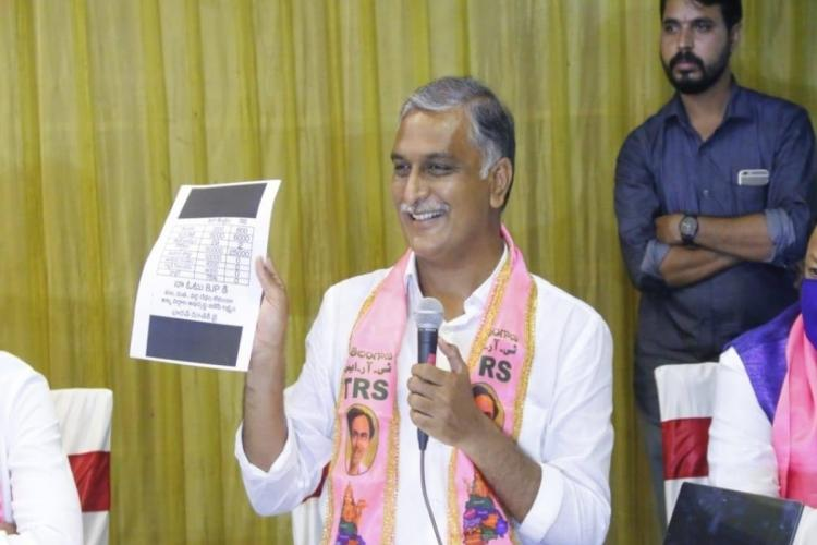Harish Rao wearing a pink scarf and a white shirt showing a document to others