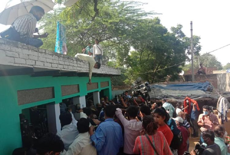 Reporters around a green building in Hathras which is the rape victims house