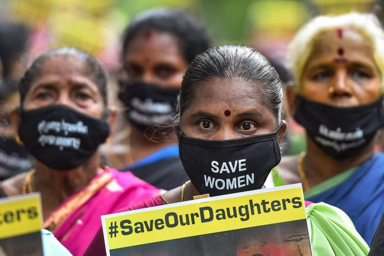 A few women are seen holding posters and wearing masks that read Save Our Daughters