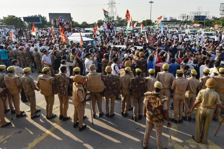 Police stop Congress leaders and supporters who were accompanying Rahul Gandhi at Delhi-Noida border on his way to Hathras to meet family members of the 19-year-old Dalit woman who died after being allegedly gang-raped. A large posse of police can be seen in the image. Some supporters are holding flags.