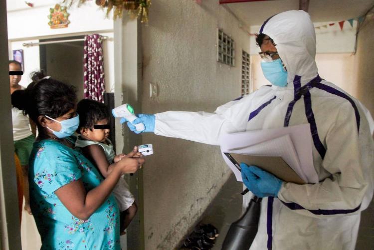 Health workers wearing personal protective equipment suits conduct door to door COVID-19 thermal screening in Mumbai