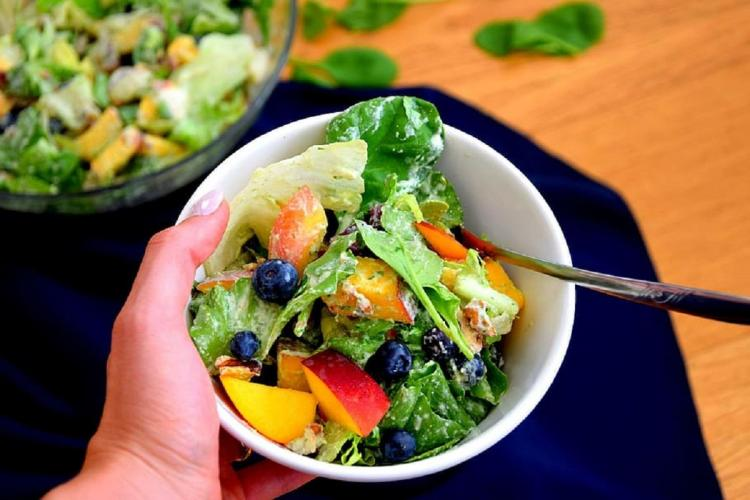 A healthy food bowl with salad comprising veggies fruits blueberries lettuce mango