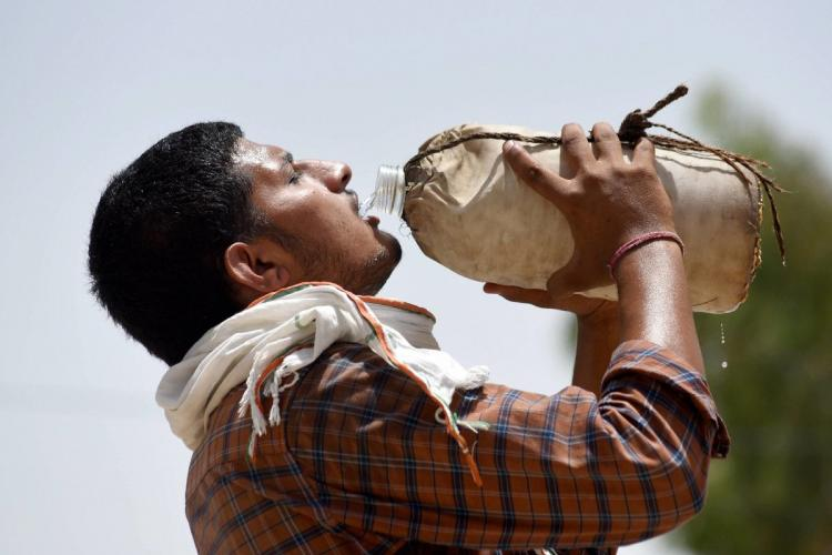 A labourer drinks water at a grain market on a hot summer day as temperature reached 48 degrees Celsius in Bikaner in May 2020