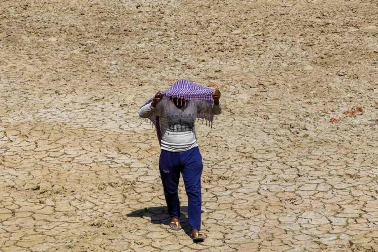A man covers his head with a cloth in the sweltering heat