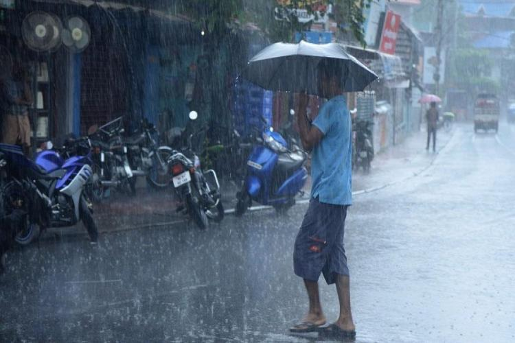 A man is crossing a nearly empty road in heavy rain with an umbrella