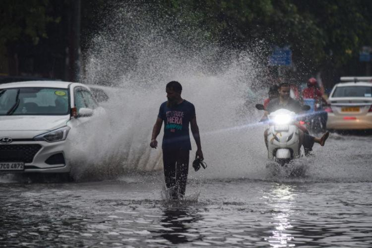 A man walking in a water-logged road holding his slippers while a car is about to splash rain water on him