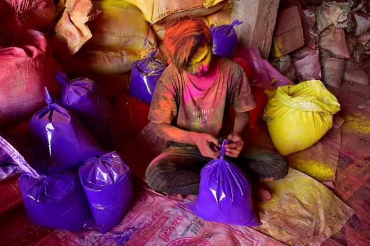 A man sitting with bags of purple and yellow holi powder