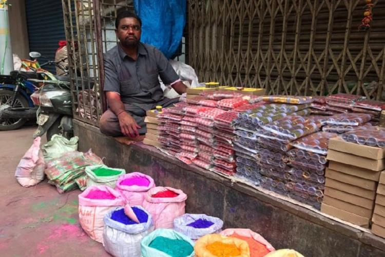 A man selling Holi colours in a street