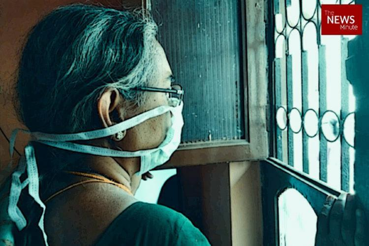 A woman wearing a mask and looking out a window