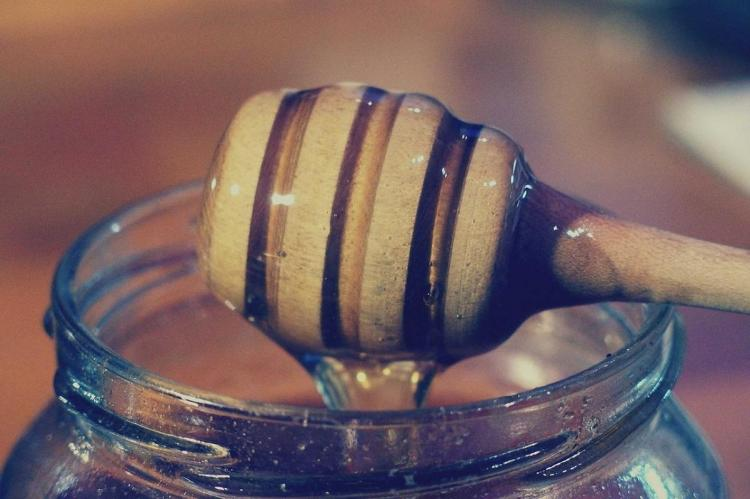 The mouth of a jar of honey with a stick dripping honey into it