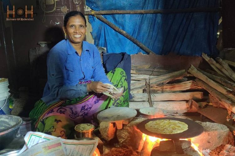 A woman in a saree and blue shirt making jowar rotis on a firewood stove