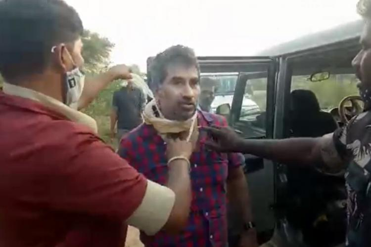 Hyderabad Dentist Behjath Hussain being rescued from kidnappers police officers help him remove cloth around his neck as he stands in a blue and red chequered shirt