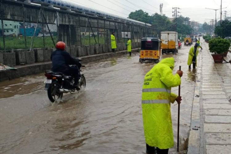 Hyderabad municipal workers wearing yellow worksuits clearing a waterlogged road as a motorist rides by on his left