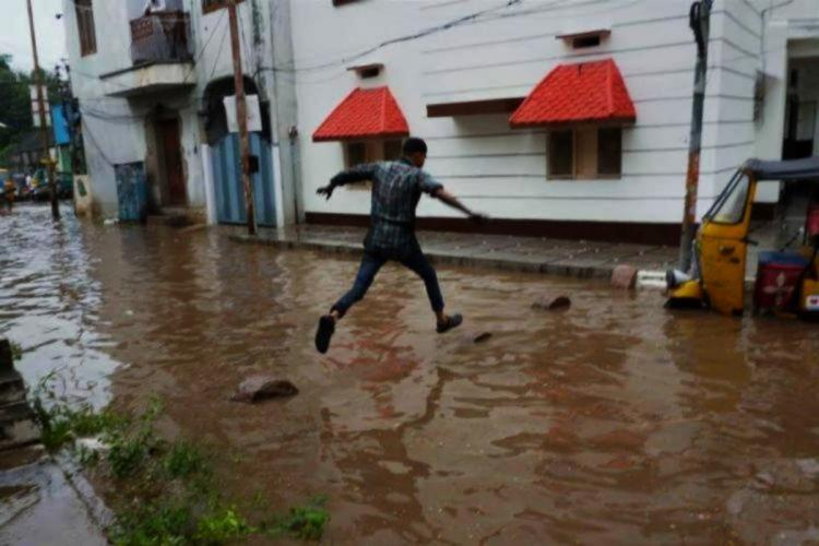 A man hopping over a waterlogged road legs suspended mid air