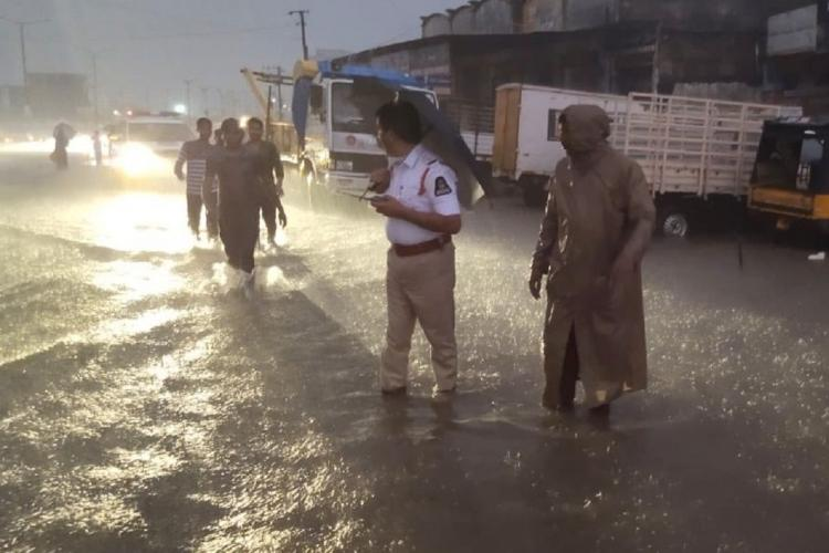 Traffic police personnel standing on waterlogged roads during Hyderabad rains